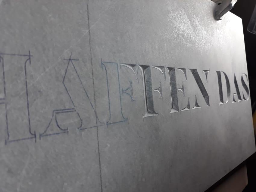 Letterkappers.be , tekst in steen, 'Wir schaffen das'